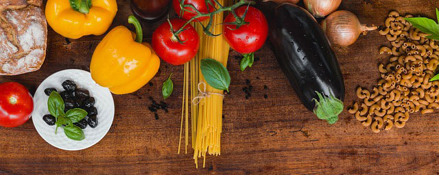 colorful picture of veggies and olives and pasta on a rustic tabletop