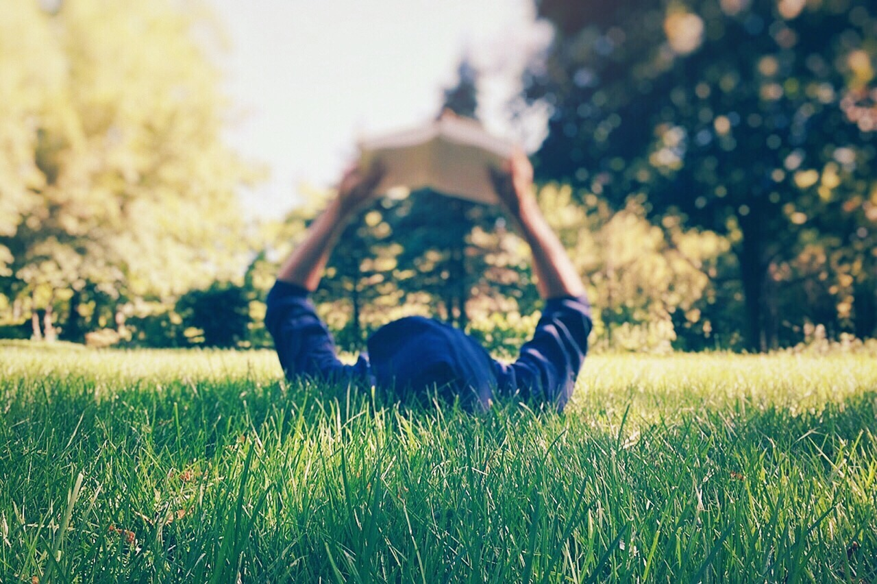 kid reading in the grass