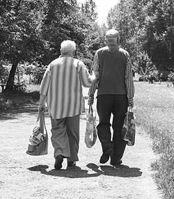 Photo of an elderly couple walking home after shopping.