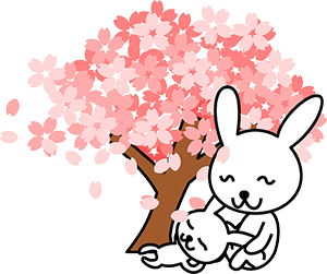 Image of two bunnies relaxing by a tree.