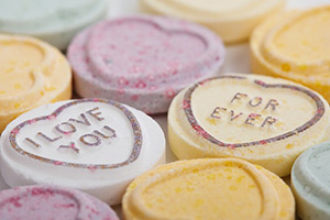 Photo of candy hearts which say I love you forever.