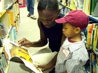 A photo of a mother and son choosing books together.